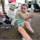 Una pequeña con prótesis recibe a un cachorro sin una pata