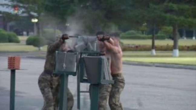 Soldados norte-coreanos quebram concreto com a cabeça em exibição para líder
